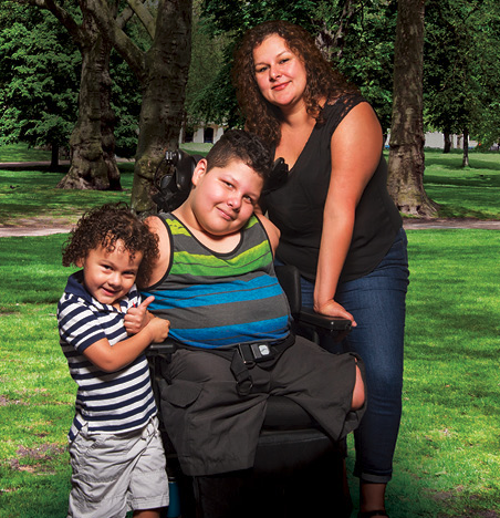 a boy in a wheelchair flanked by his mother and younger brother