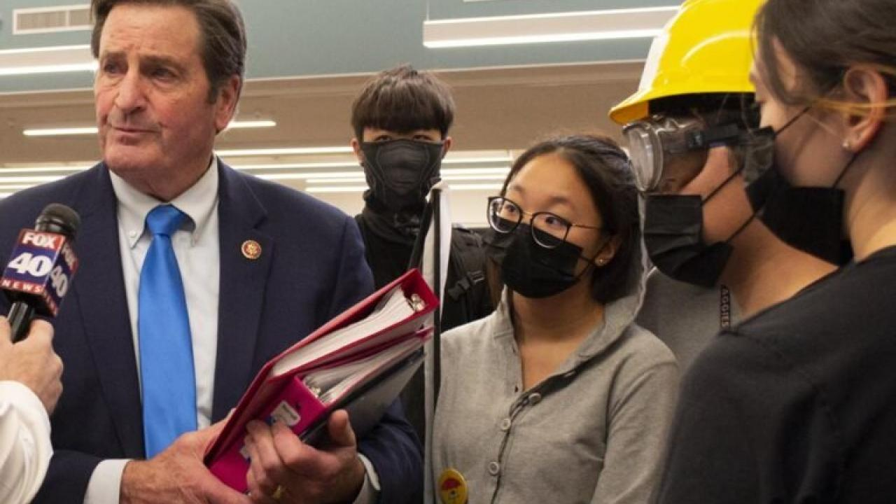 man talking to reporters with students in masks