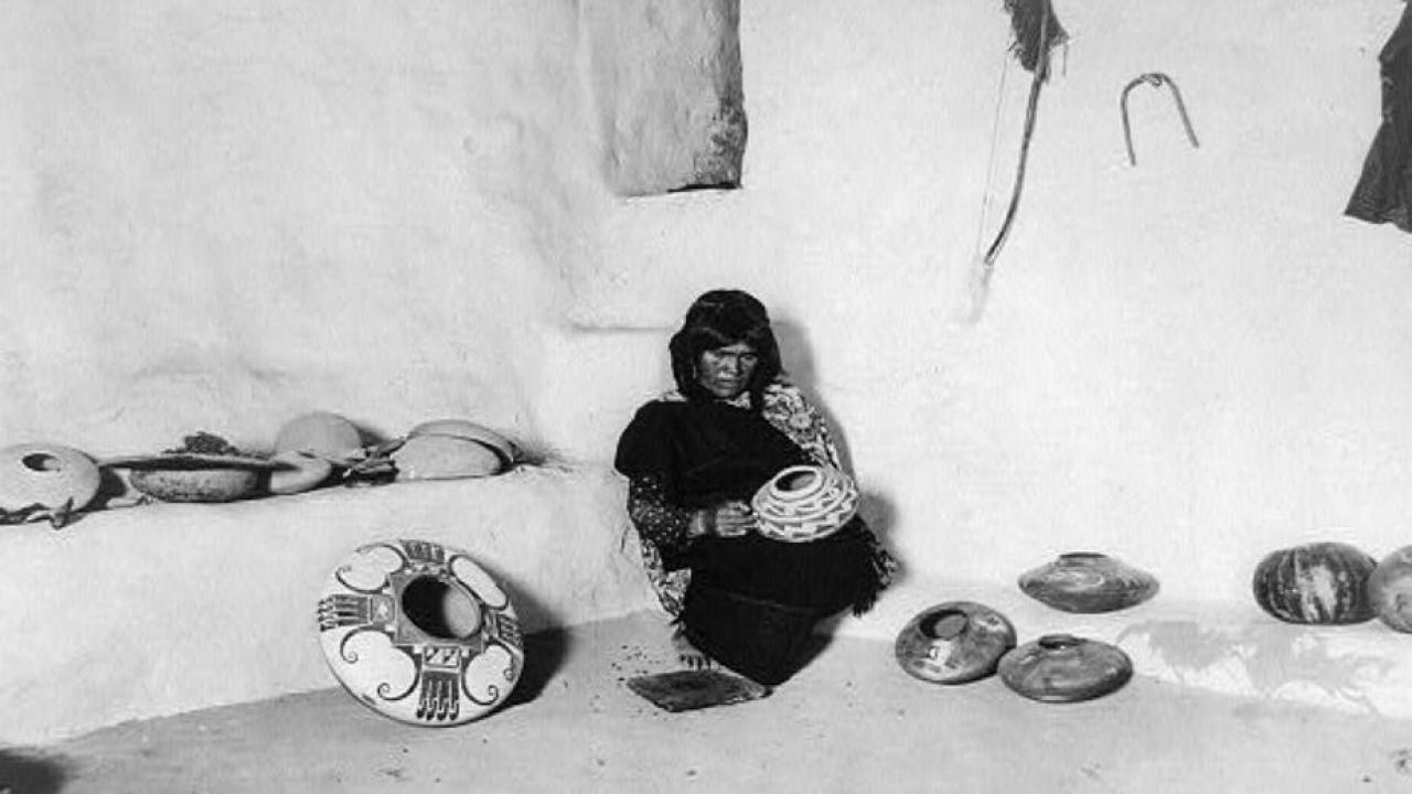 black and white photo of a woman in a primitive structure.