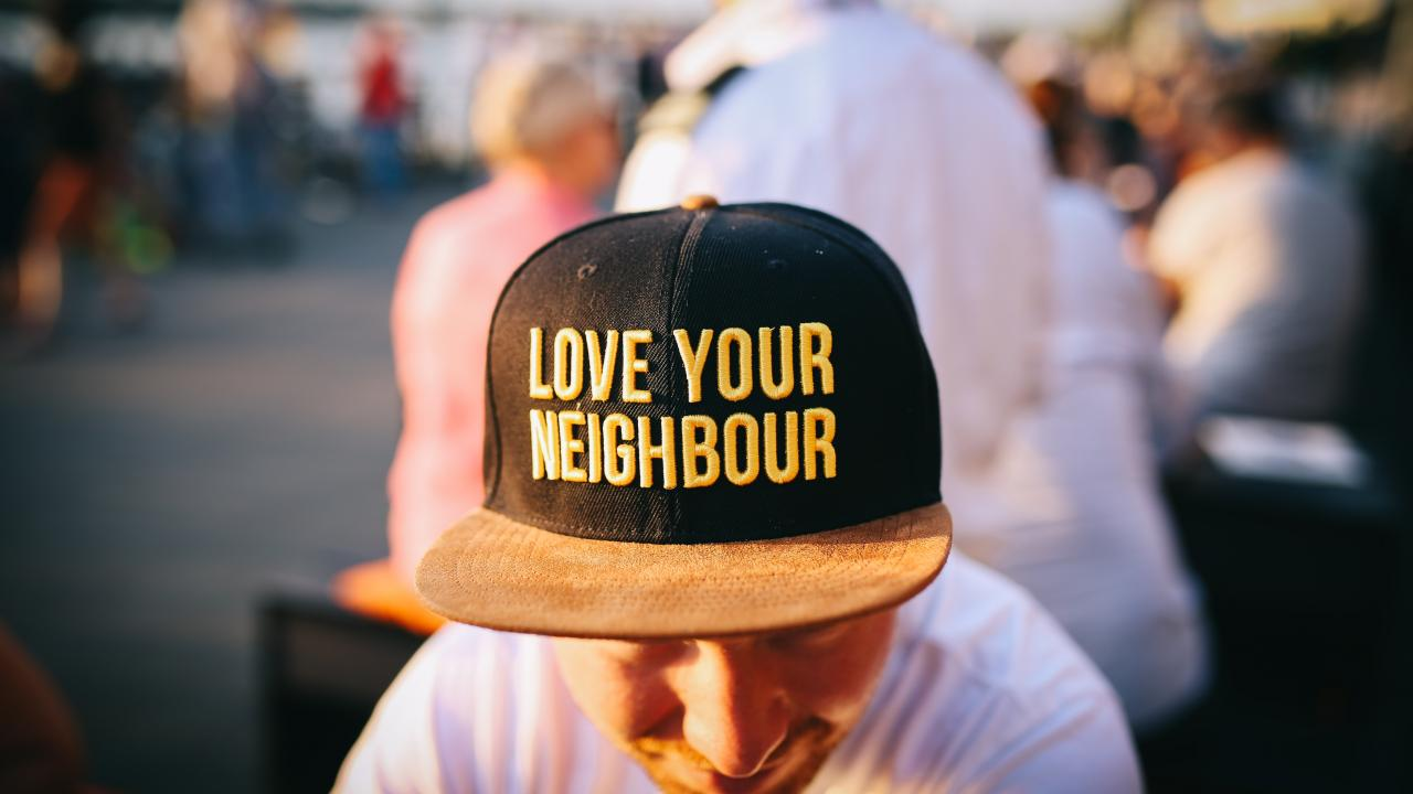 "man wearing a hat that says ""love your neighbor"""