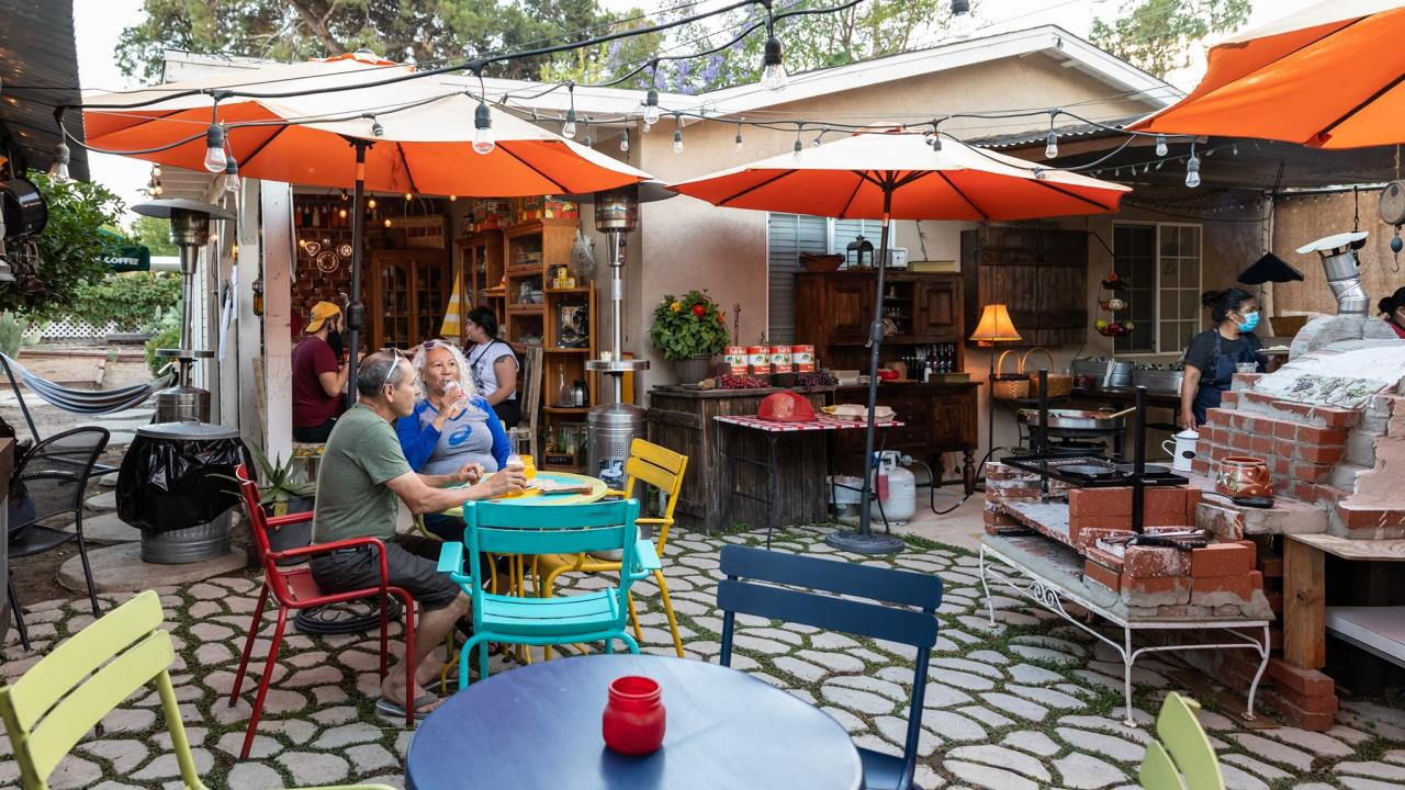 a patio backyard with umbrellas and a couple eating dinner