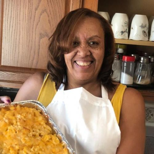 a woman holding up a home-cooked casserole