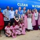 "Group of people standing in front of a large truck that reads ""clean water"""