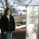 woman smiling while standing in front of a greenhouse at a school