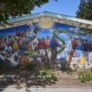 "colorful mural on a side of a building that features different people together as a group with the words ""la comunidad"" and ""a united community"""