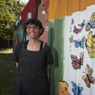 woman standing next to a butterfly mural