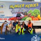 "A group of individuals pose in front of a large truck featuring fruits and the words ""Hunger Heroes Feed Hope!"""