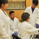 Four students in a white lab coat testing a lab equipment