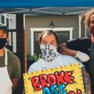 three men with masks and cooking aprons pose for a photo