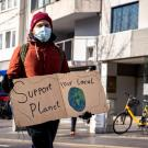 a man in a mask holding a sign that says support your local planet